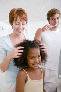 White mother braiding black daughter's hair while father brushes his teeth,