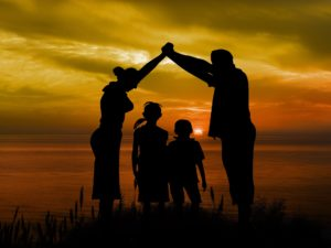 Mother and Father standing over two children, creating an arch by joining their hands.