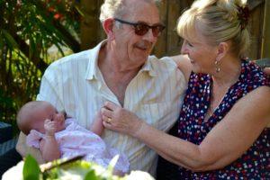 Grandparents holding their grandchild.