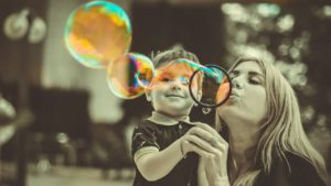 Young boy holding a bubble wand while his mother blows bubbles.