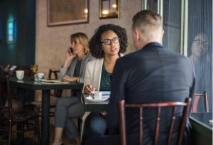 An African American Woman and White Male sitting in a cafe having an argument.