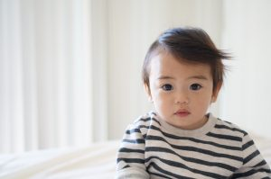 Asian baby wearing a striped shirt, sitting alome, looking at the camera.