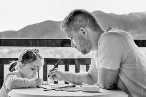 Black and white picture of a father and young daughter drawing on a porch overlooking some mountains.