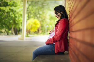 Lone pregnant woman in red jacket sitting on a bench, leaning against a brick wall