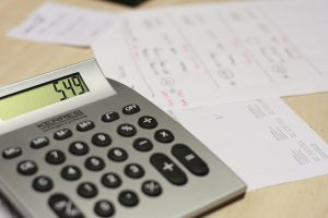 Calculator sitting next to several pieces of paper with numbers jotted down.