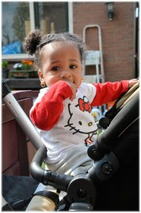 Black child sitting in a stroller wearing a Hello Kitty shirt.