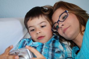 Mother and son snuggle close and look at a digital camera.