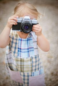 Little girl holding a camera up to her eye.