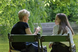 Mother and daughter talking on bench.