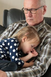 Family member adopt: A grandfather with gray hair, glasses, and a plaid shirt sleeping in a chair with his granddaughter wearing a blue and white polka dot shirt and sucking on her thumb sleeping in his lap.