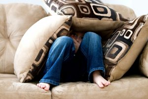 A boy in a blue denim pants is sitting on a couch, hiding under three pillows because he's struggling with adoption
