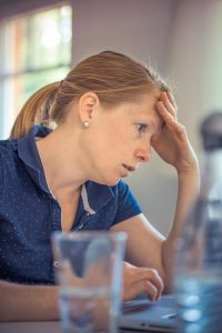Woman looks sad while sitting at a counter with her head in her hand after dealing with rude questions.