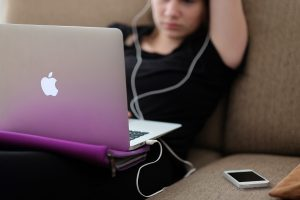woman wearing black and sitting on a couch with her Apple laptop on her lap and her iPhone sitting next to her.