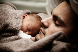 A baby adopted from a local adoption agency sleeping on his father's chest.