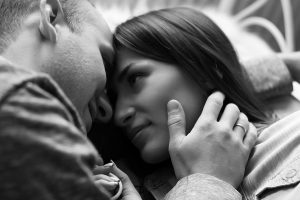 Saving for Adoption blog image. A man and woman embrace while laying down. Their foreheads are touching as they look into each other's eyes.