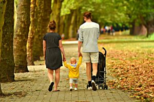 Foster Care Blog Image: A family of three walking down a brick sidewalk. The child is in the middle holding his parents' hands.