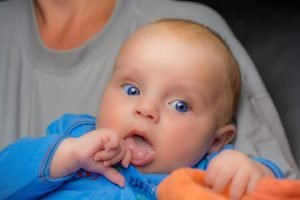 Adjusting to Life as New Parents After Adoption Blog Image. A closeup of a baby with bright blue eyes.