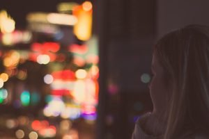 Post Adoption Depression Syndrome Blog Image: A young woman looking out a window. The lights outside are a blurr.
