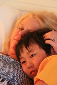 How to Talk to An Adoptive Family blog image: a mother laying on a bed cuddling with her adopted son.