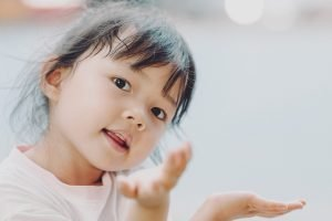 Should an Adopted Child Know Their Biological Parents? article image: A young girl about 4 years old looking over her shoulder at the camera.
